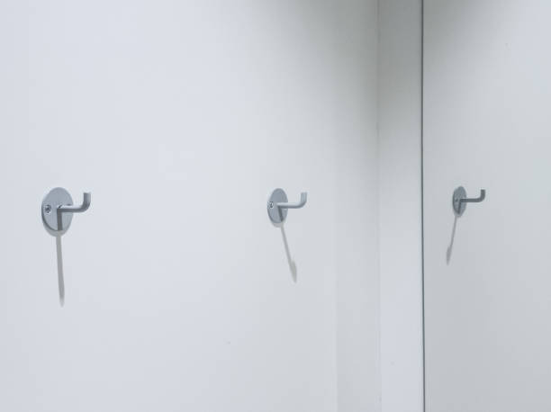 two clothes hooks on a white wall with copy space