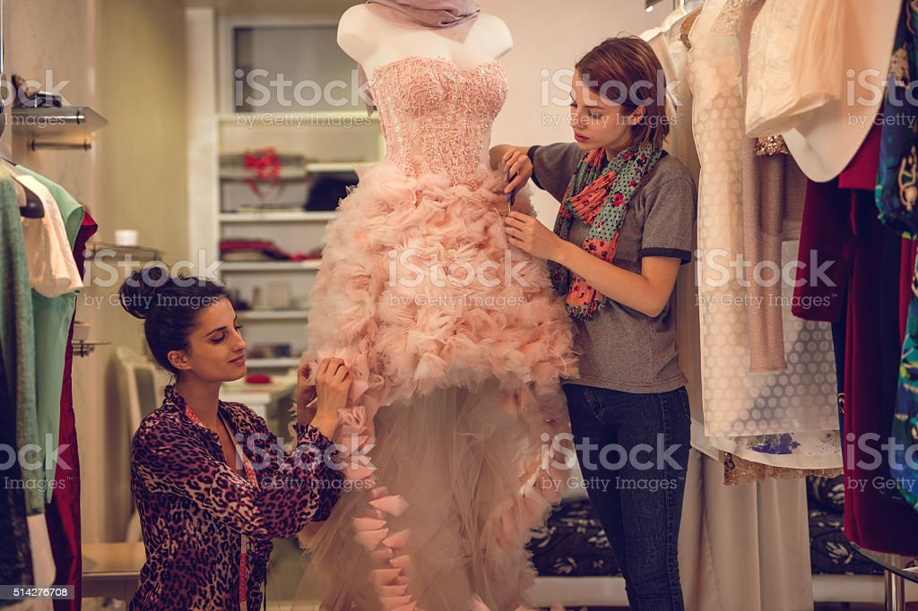 Two clothing designers working on mannequin in fashion design studio. stock photo