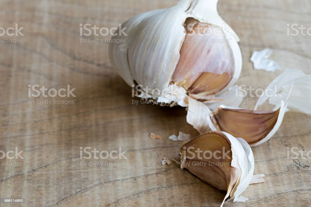 Two cloves of garlic with a head of garlic in the background stock photo