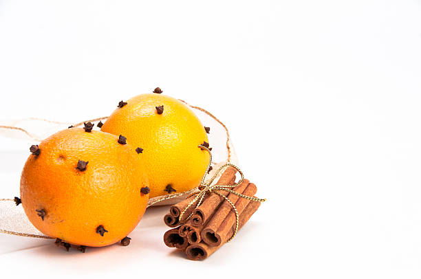 Two cloves-decorated oranges and cinnamon sticks stock photo