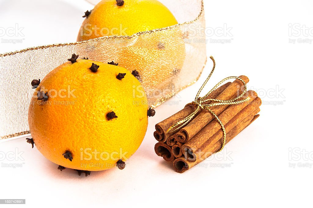 Two cloves-decorated ornages, cinnamon sticks and riboons stock photo