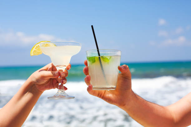 two cocktail glasses in man and woman hands - margarita drink stock photos and pictures