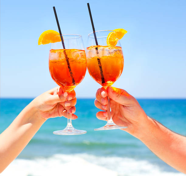 Two cocktail glasses in the hands on sea background - foto stock