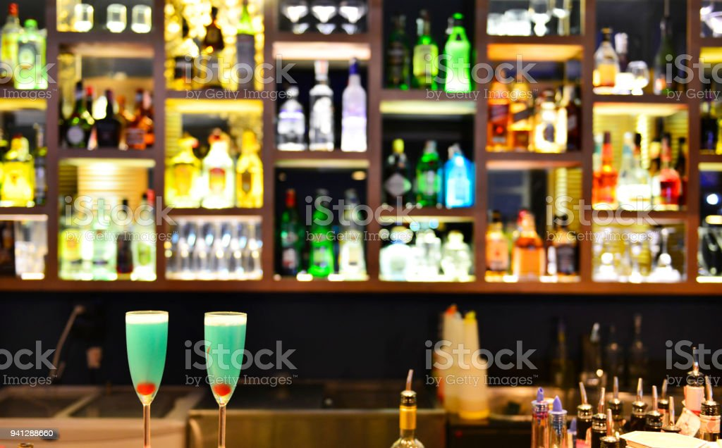 Two Cocktail glasses with Bottles of spirits and liquor on bar counter stock photo