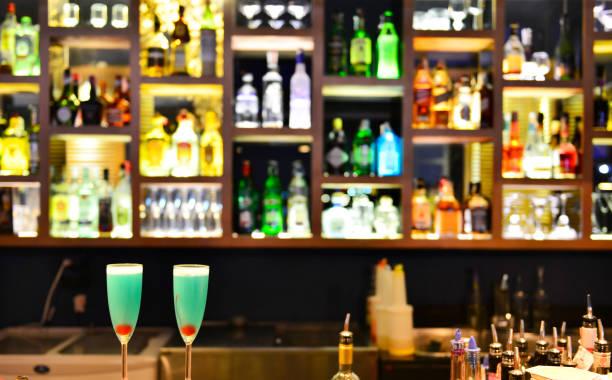 zwei cocktail-gläser mit flaschen spirituosen und liköre auf bartheke - whisky test stock-fotos und bilder