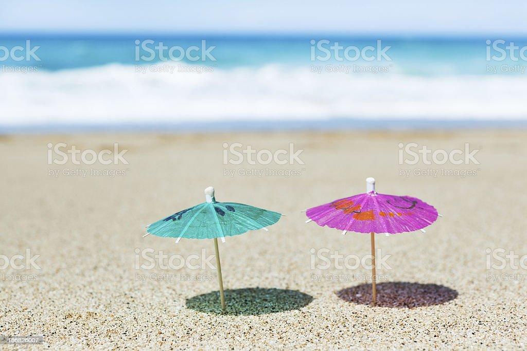 Two Cocktail Umbrellas on Tropical Paradise Beach Hz stock photo