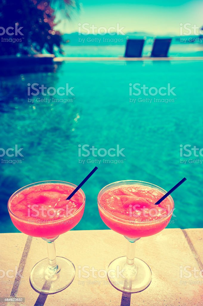 Two cocktails beside a resort swimming pool stock photo