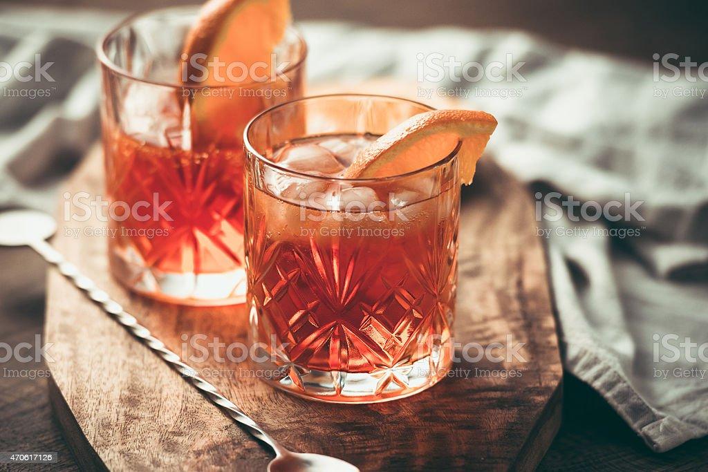 Two cocktails garnished with orange slices on wooden bar top