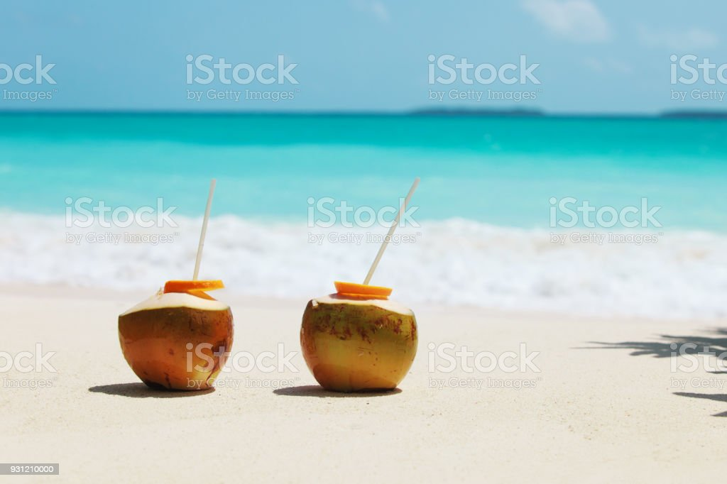two coconut drinks on tropical beach vacation stock photo