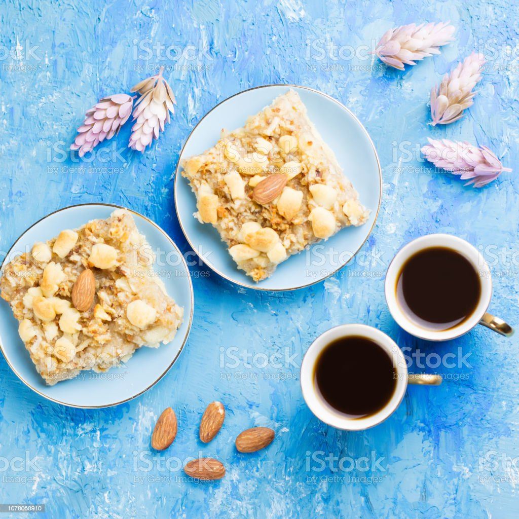Two coffee cups, coffee grinder and apple pie on blue artistic background. stock photo