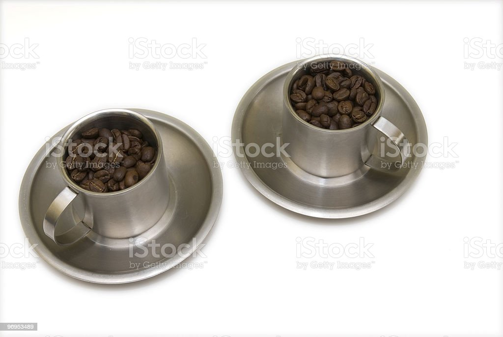 Two coffee cups on saucers filled with beans. royalty-free stock photo