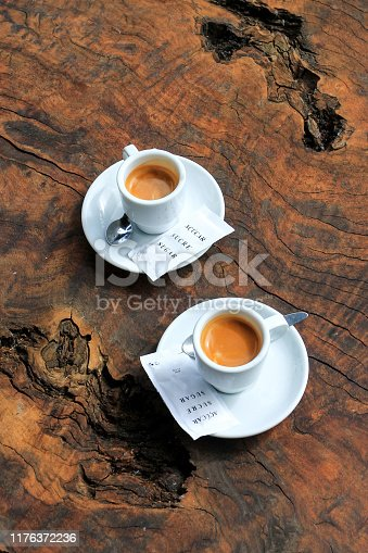 Two coffee espresso white cups with sugar sachets on natural brown wooden table, top view, vertical orientation