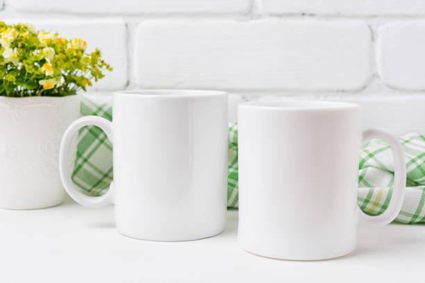 Two coffee mug mockup with yellow and green flowers stock photo