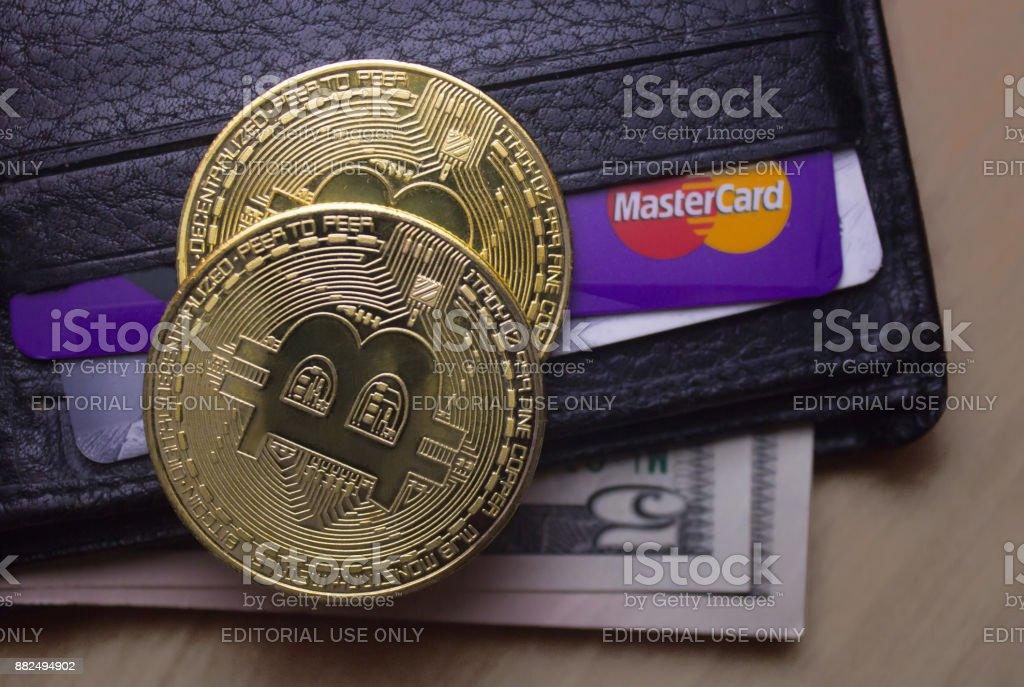 Two coins of bitcoin on a wallet with dollars stock photo