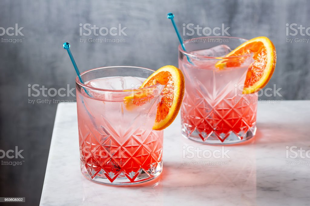 Two Cold Blood Orange Gin and Tonic Cocktails on Marble Bar Counter stock photo