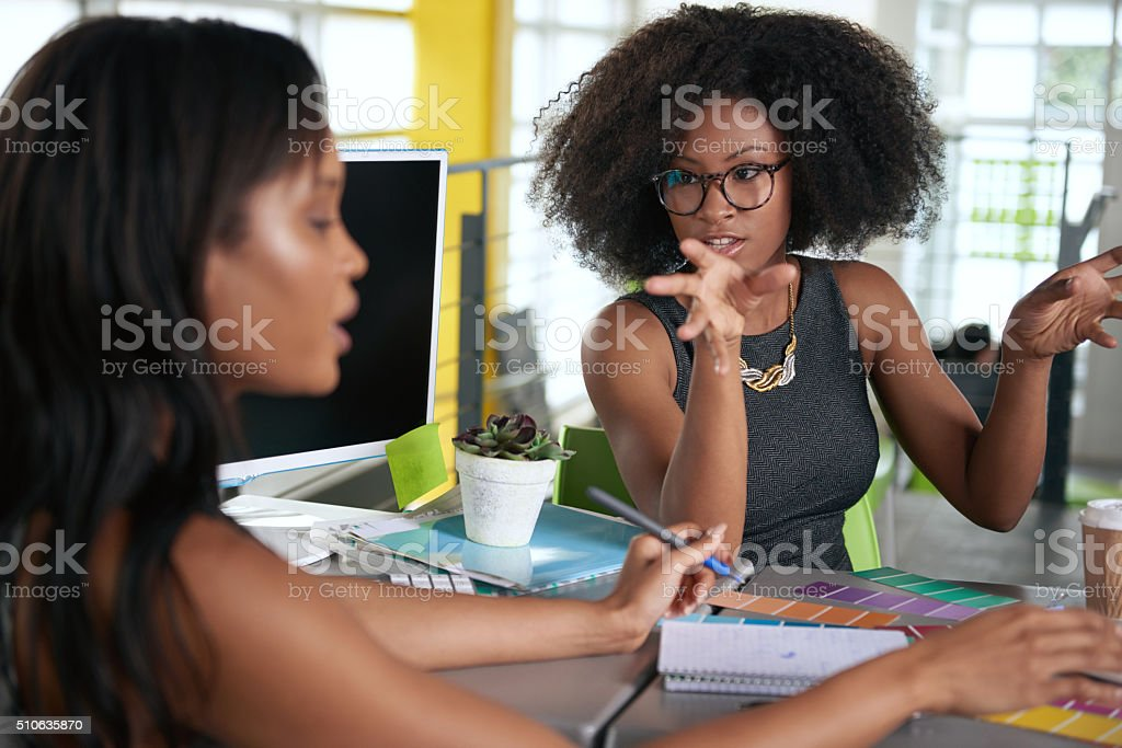 Two  colleages discussing ideas using a tablet and computer stock photo