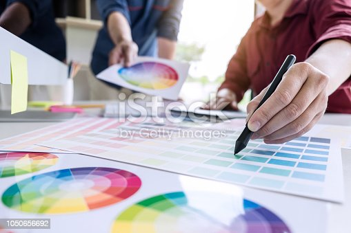 istock Two colleague creative graphic designer working on color selection and color swatches, drawing on graphics tablet at workplace with work tools and accessories 1050656692