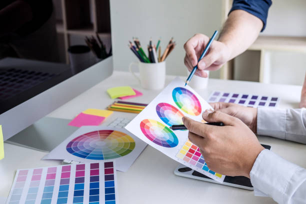 Two colleague creative graphic designer working on color selection and color swatches, drawing on graphics tablet at workplace with work tools and accessories stock photo