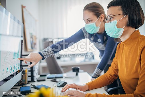 Two female colleagues at work wearing face protective mask, to protecting themselves against corona virus
