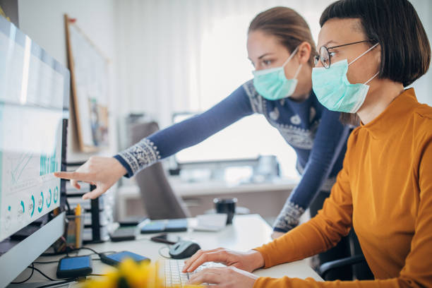 Two colleagues at work wearing face protective mask, to protecting themselves against corona virus stock photo