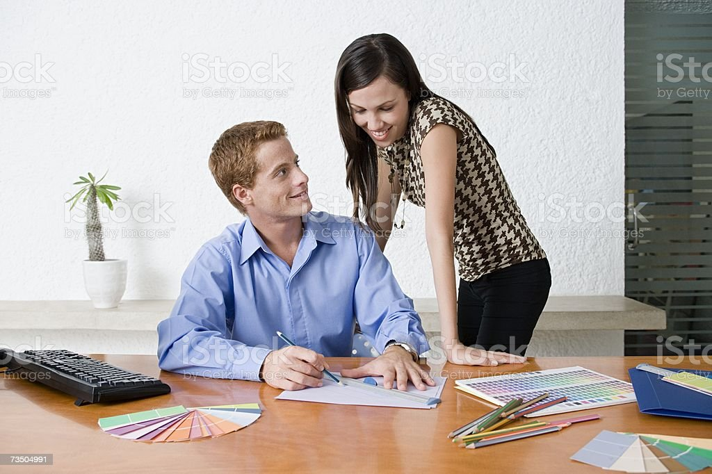 Two colleagues flirting in office royalty-free stock photo