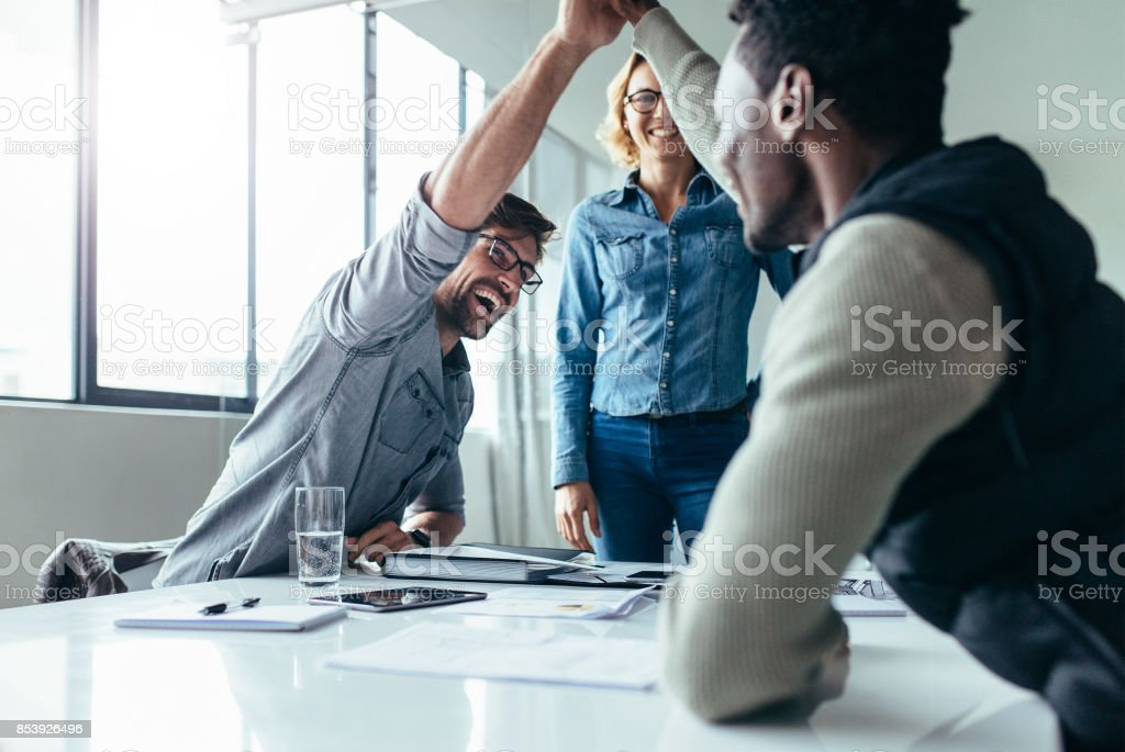 Two colleagues giving high five during meeting - foto stock