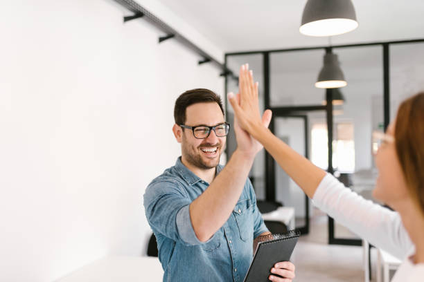 two colleagues high-five. - business celebration stock pictures, royalty-free photos & images
