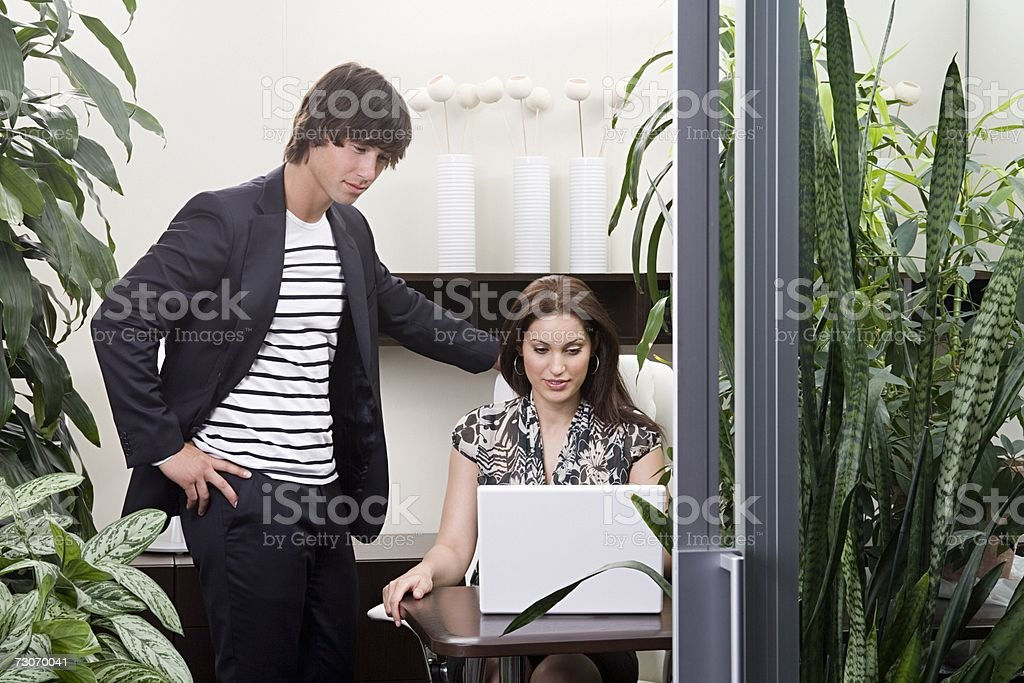 Two colleagues in an overgrown office stock photo