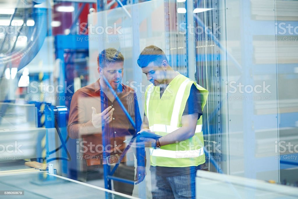 Two colleagues on factory using digital tablet stock photo