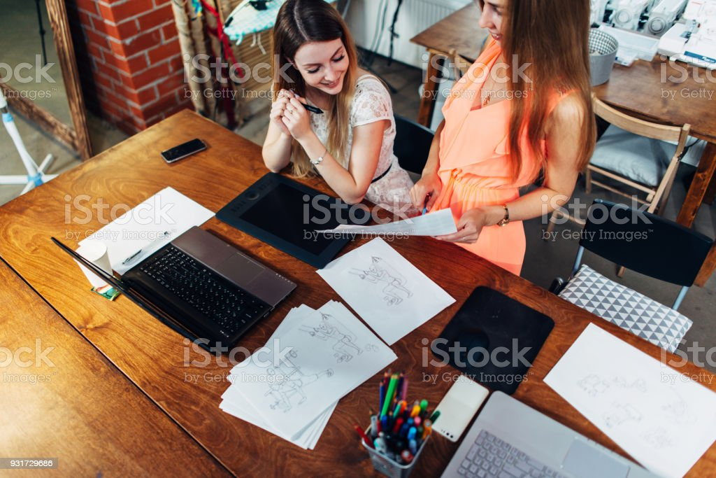 Two colleagues sharing creative ideas discussing new designs in modern studio stock photo
