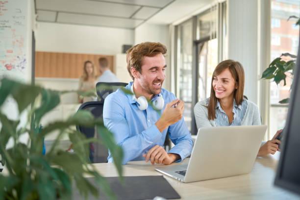 Zwei Kollegen sitzen im Büro und arbeiten am Laptop. – Foto