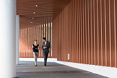 Two ethnic colleagues talk and walk together on their way to a meeting. They are in the outdoor corridor of a modern conference center.