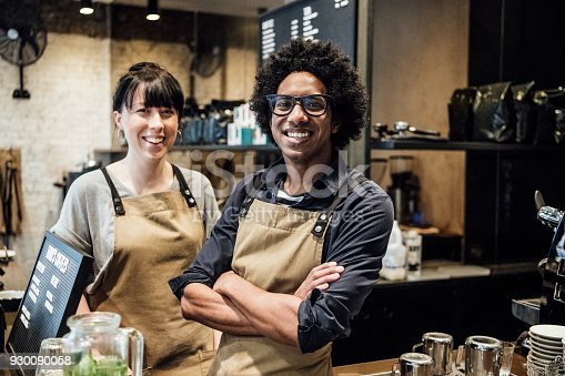 istock Two colleagues working in coffee shop smiling towards camera 930090058