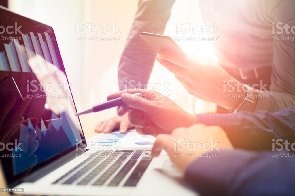 Two colleagues working on new global financial strategy plan using laptop and smartphone.Modern business team innovation concept.Project meeting at office with virtual graph and chart data interface stock photo