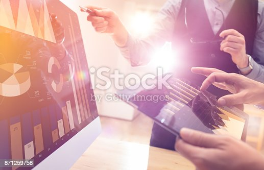 istock Two colleagues working on new global financial strategy plan using tablet and laptop.Modern business team innovation concept.Project meeting at office with virtual graph and chart data interface 871259758