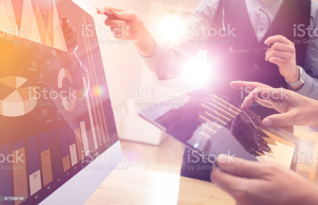 Two colleagues working on new global financial strategy plan using tablet and laptop.Modern business team innovation concept.Project meeting at office with virtual graph and chart data interface stock photo