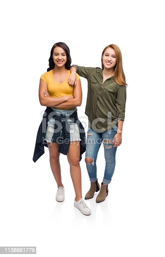 Two latin college female friends wearing casual clothing on has arm over the others shoulder.
