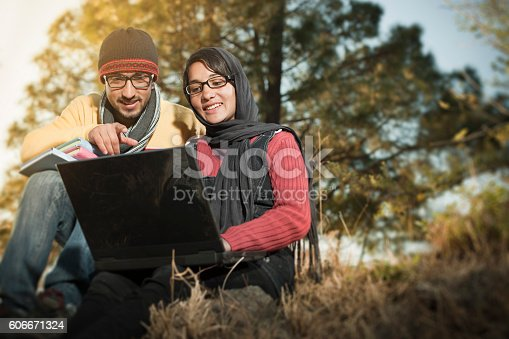 istock Two college students are using laptop together in hilly area. 606671324