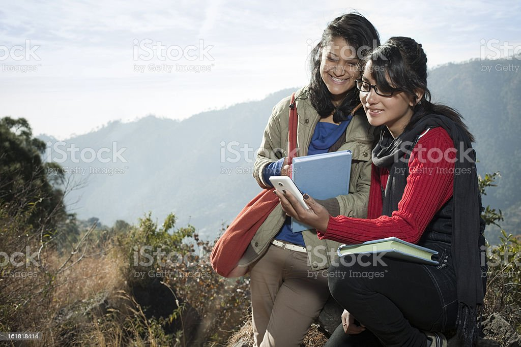 Two college students reading book together in mountain area. stock photo