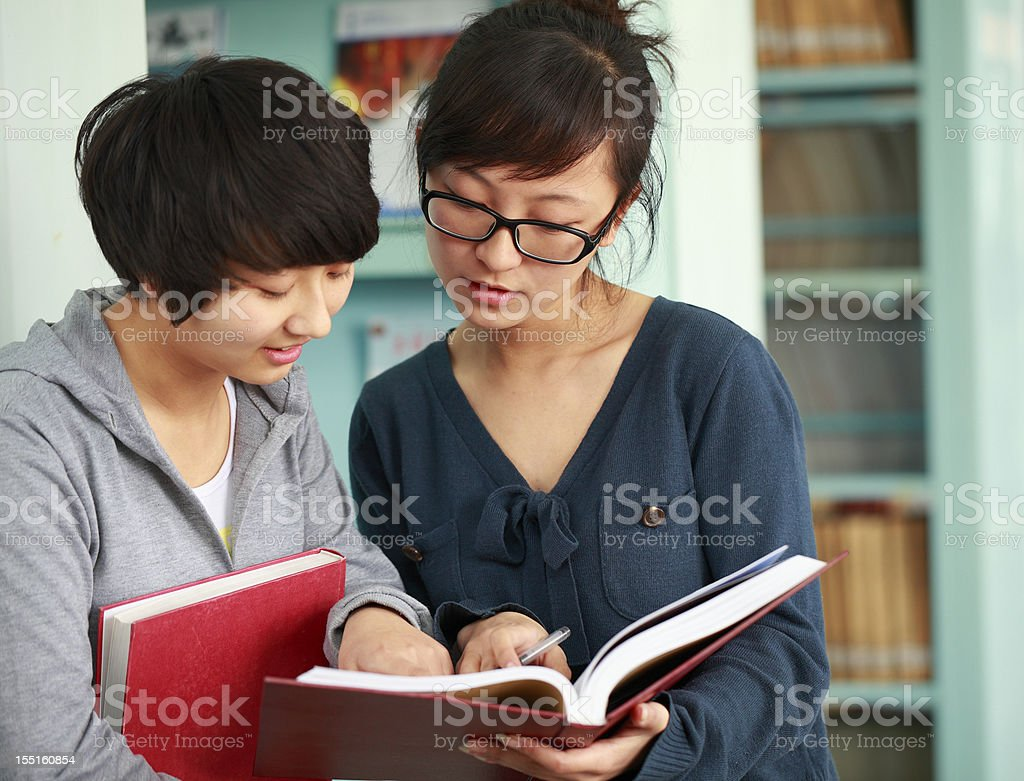 two college students reading book together in the library royalty-free stock photo