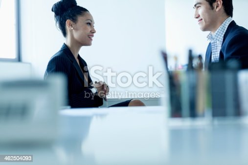 496441730 istock photo Two colleges smiling and talking by the desk in office 462504093