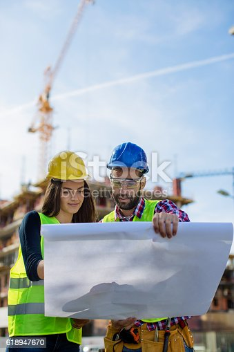 617878058 istock photo Two collegues lookibng at blueprints at construction site 618947670