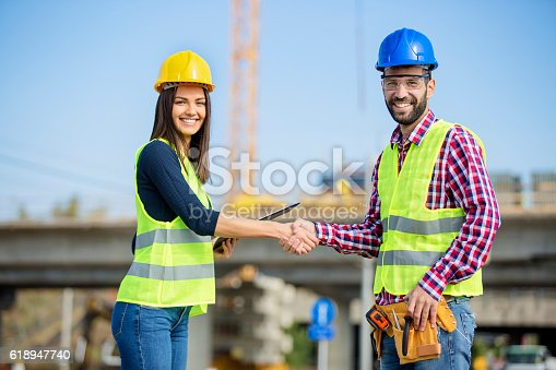 617878058 istock photo Two collegues shaking hands at construction site 618947740