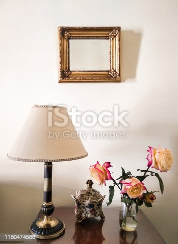 Two color roses in glass jar with water placed on table of a house with vintage decoration. Freshly picked flowers at home with classic decoration.