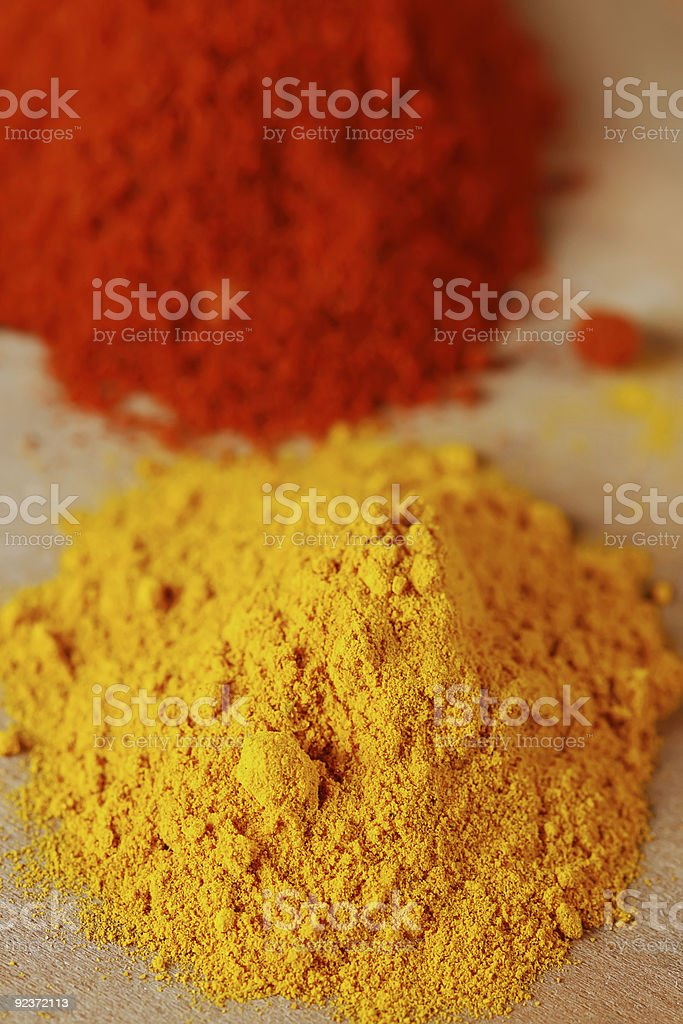 two color spices - pile of ground turmeric and paprika royalty-free stock photo