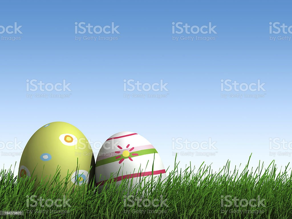 Two colored Easter eggs in green grass against a blue sky royalty-free stock photo