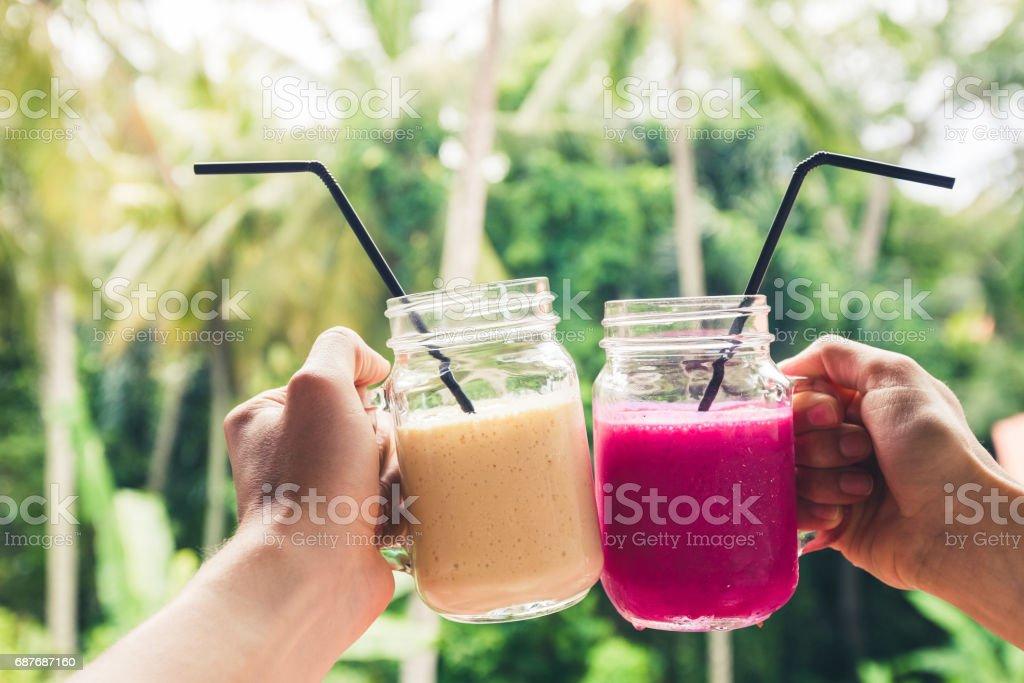 Coloridas dos frutas sacudidas en las manos. Verano y ambiente tropical. Frío bebidas mezcladas, plátano y Dragón batido de fruta. Brindar por las manos de la pareja - foto de stock