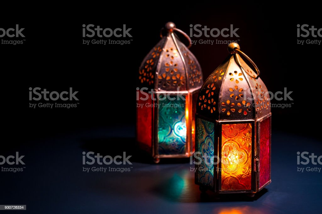 Two colorful oriental Lamp lanterns burn with candles with color reflection on dark black background for Ramadan and other islamic muslim holidays stock photo