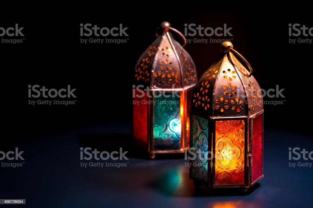 Dos linternas coloridas de lámpara orientales queman con velas con la reflexión de color sobre fondo negro oscuro para Ramadan y otras festividades musulmanas islámicas - foto de stock