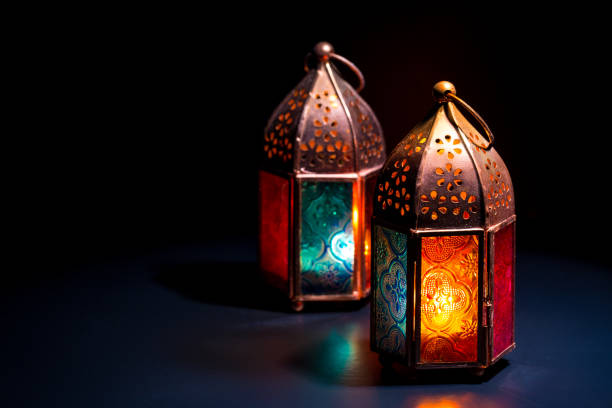 two colorful oriental lamp lanterns burn with candles with color reflection on dark black background for ramadan and other islamic muslim holidays - eid stock pictures, royalty-free photos & images